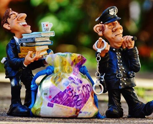 tax evasion police handcuffs